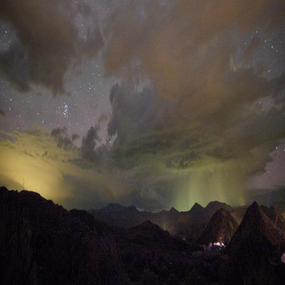 A mountainous scene is shown at night, with a small, glowing city in the lower right-hand corner. The mountains are dwarfed by an enormous sky, peppered with patchy clouds and swaths of stars. The sky has an unnatural glow (literally), with fields of yellow-green and orangish light, indicating light pollution.