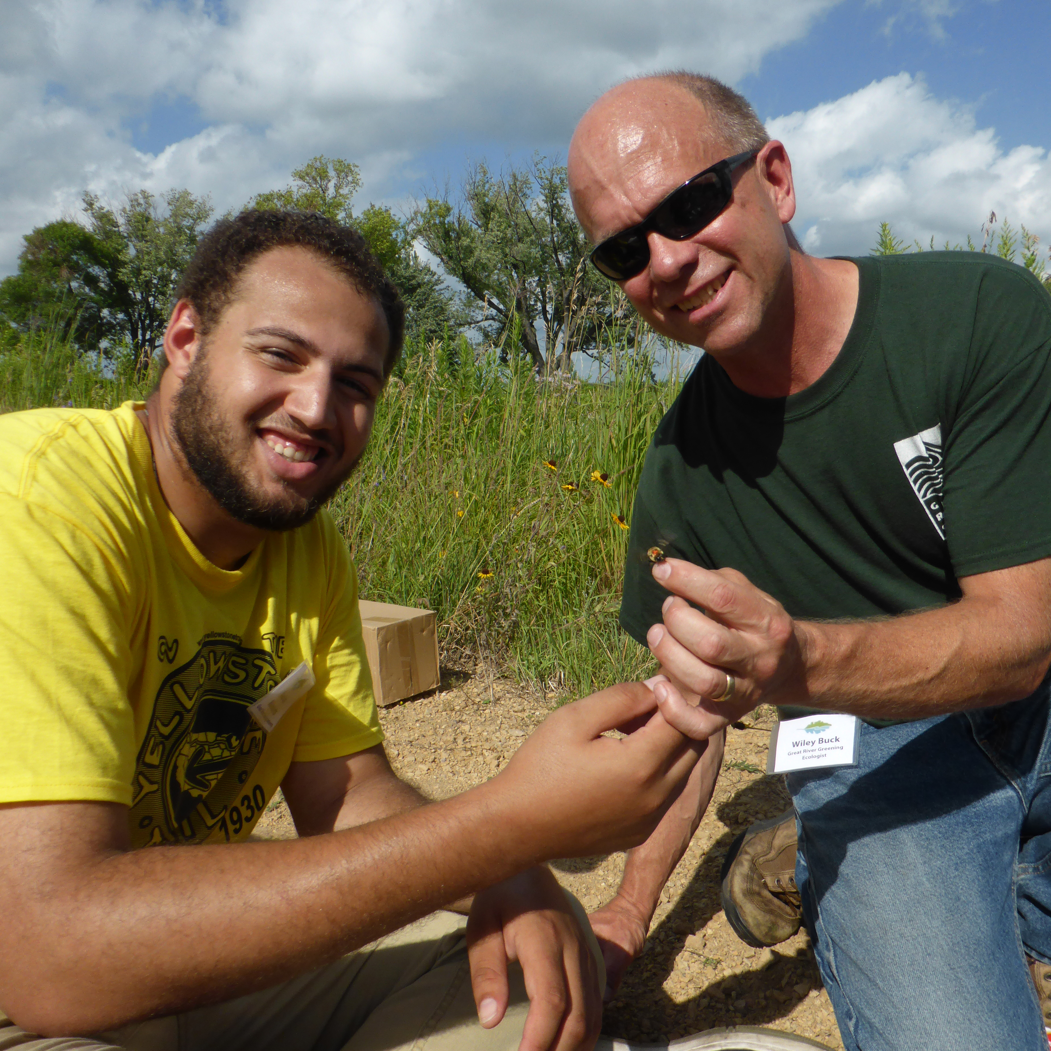 Two people, one a young man with dark skin, and one an older man with pale skin, have their hands close together as they show off a bumble bee they caught as part of a community science effort.