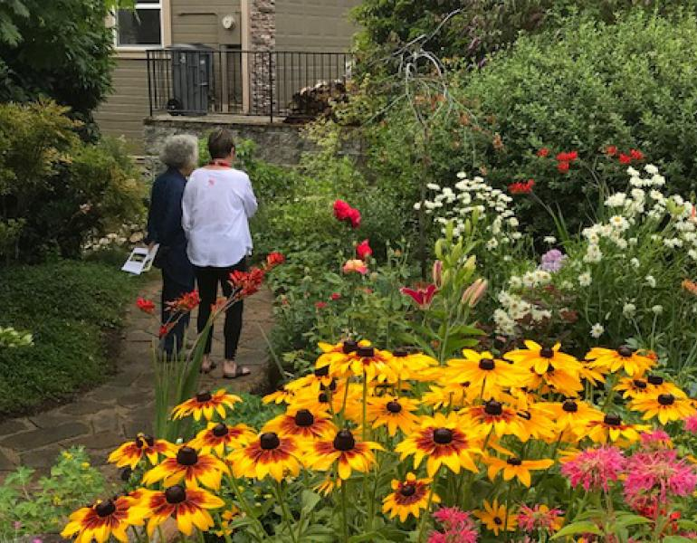 Two women walk through a garden with abundant, colorful flowers.