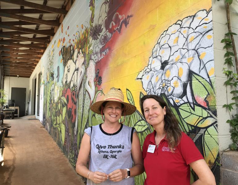 Two women in grey and red shirts stand in front of a colorful mural that shows flowers and insects at the State Botanical Garden of Georgia