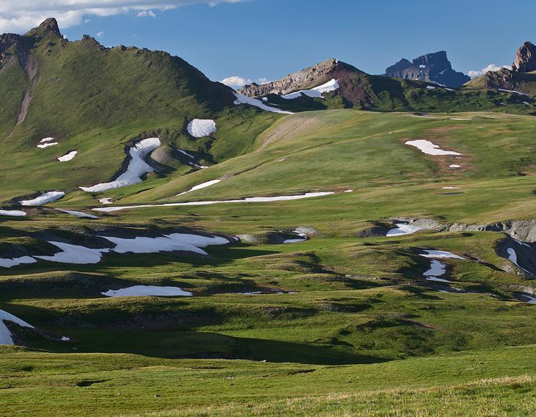 Patches of snow remain all year on the green grass slopes of the San Juan Mountains of Colorado