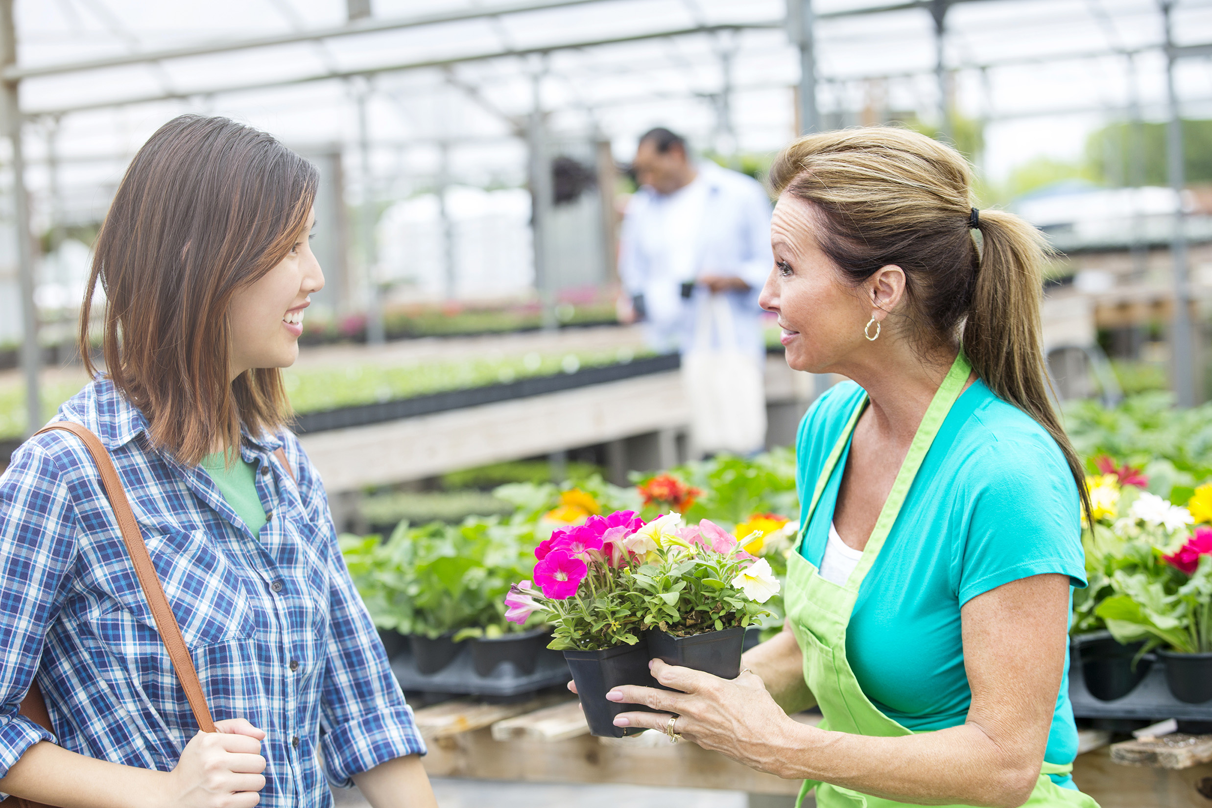 Two women stand in the middle of a garden center talking about plants