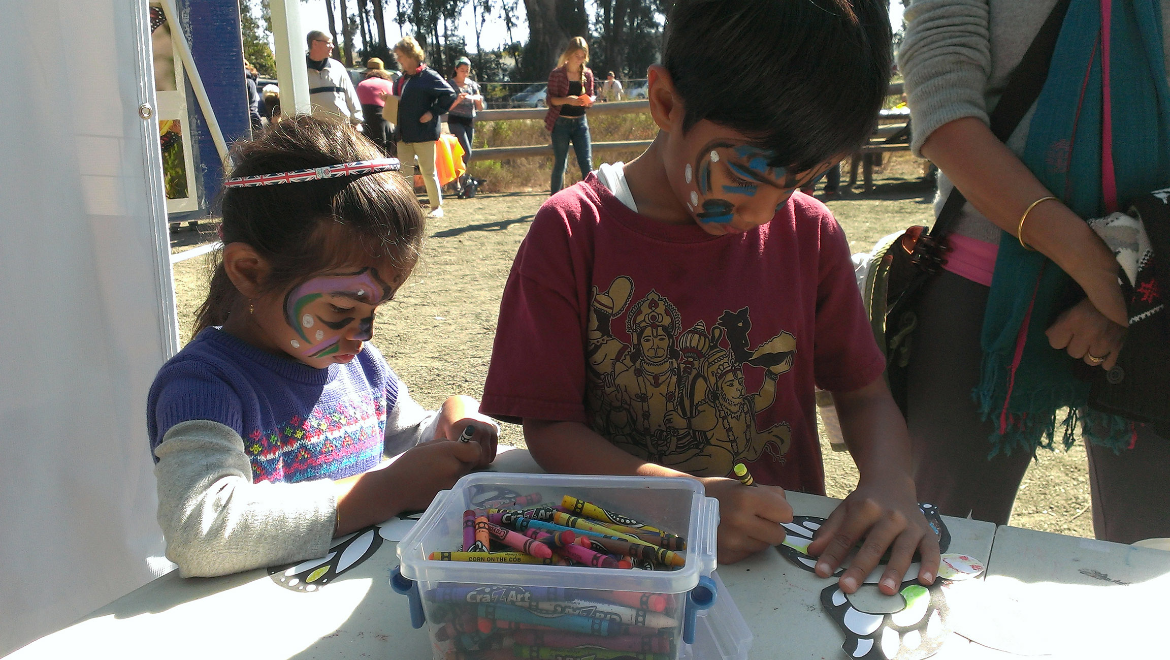 Two children, their faces decorated with face paints, concentrate on coloring monarch butterfly drawings