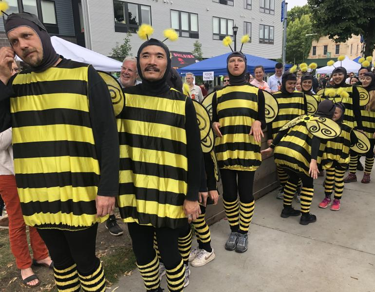 A long line of people of diverse ages, genders, and races are all sporting bright yellow and black-striped bee outfits in an outdoor festival setting.