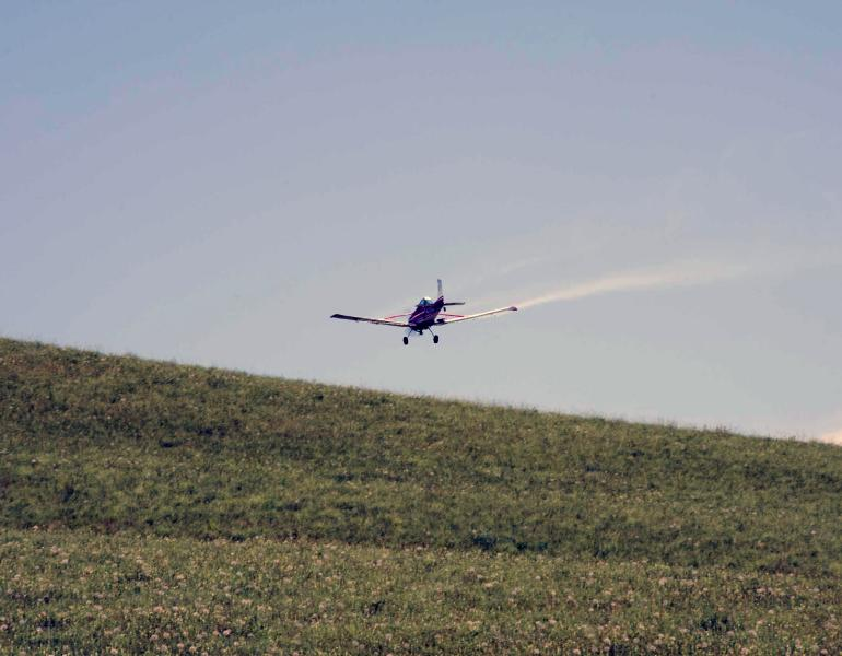 A small aircraft flies close to the ground as it sprays insecticides on rangeland